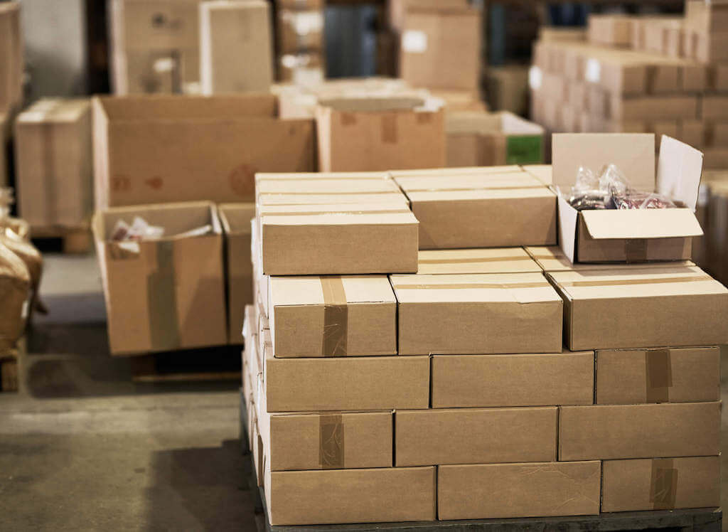 A large pile of boxes wait to be shipped by multiple carriers