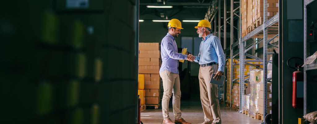 Two men shaking hands in a warehouse