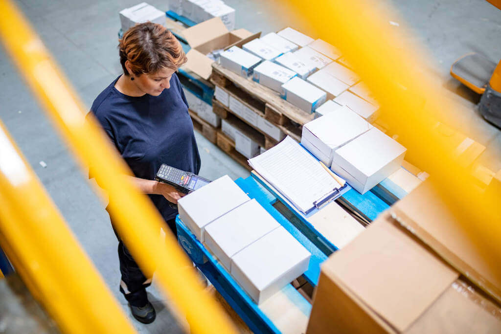 A 3PL warehouse worker scans a package