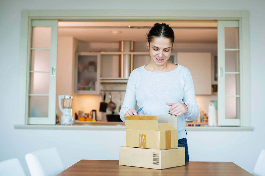 A woman unpacks a kit that she has received as part of a subscription box service