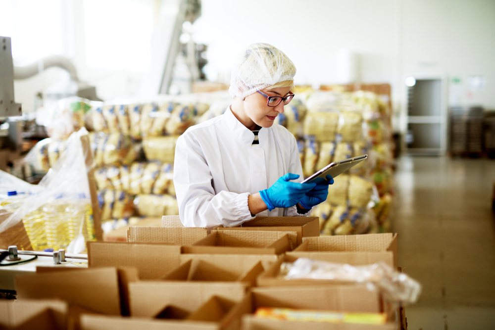 A worker packs boxes of food to ship.